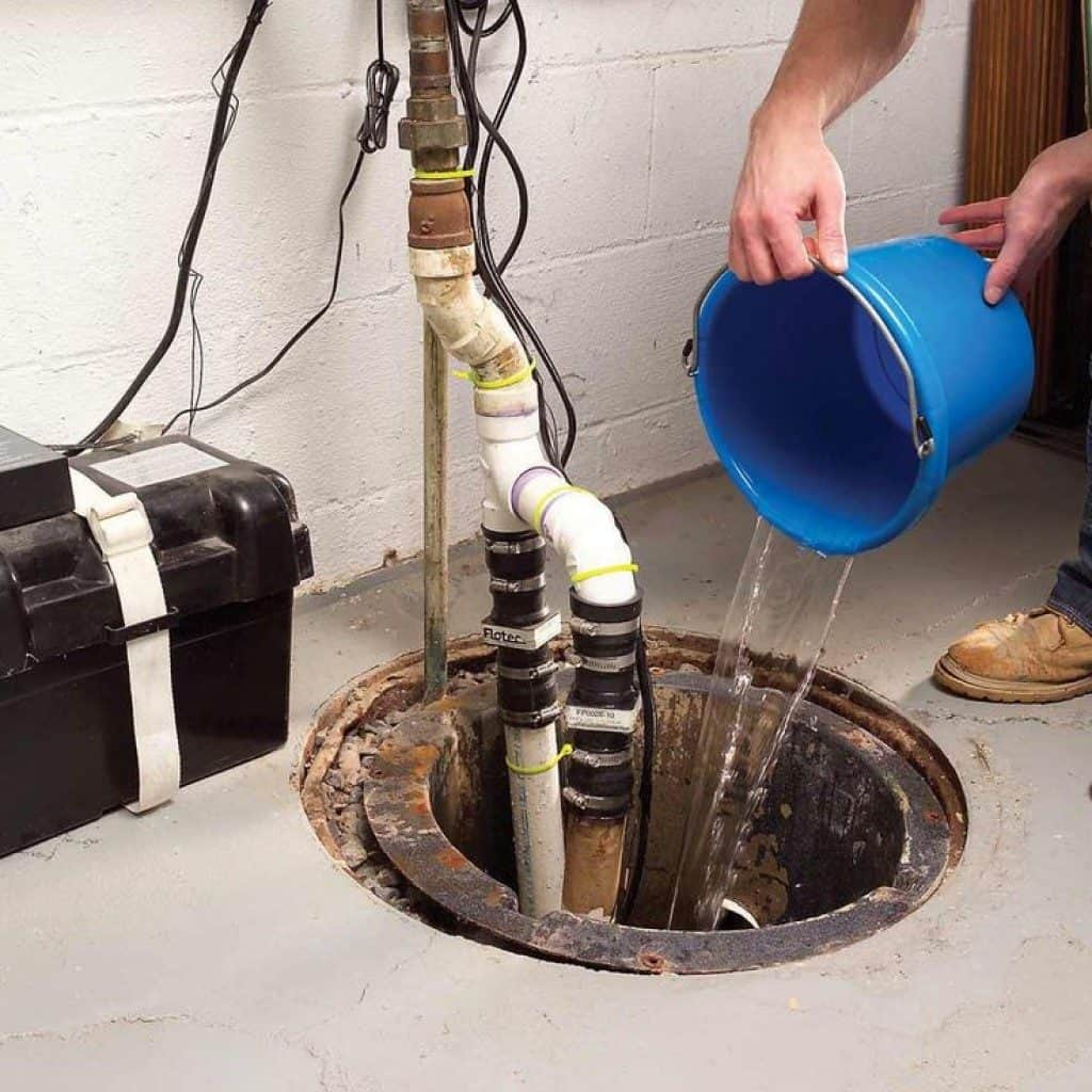 Man pouring a bucket of water in a sump pump